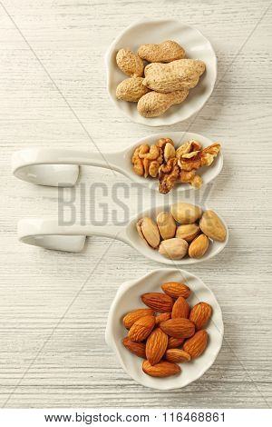 Walnut kernels, almonds, pistachios, peanuts in the ceramic spoons and bowls on the wooden table