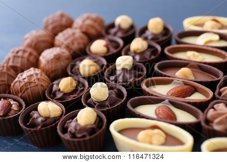 Delicious chocolate candies on blue wooden background, close up