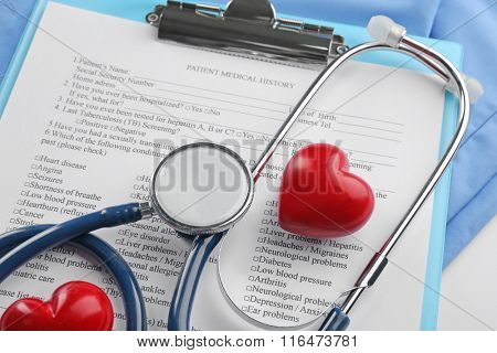 A stethoscope, coat, plastic heart and clipboard, close-up