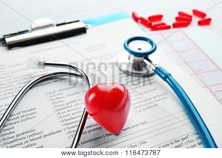 A stethoscope, pills, plastic heart and clipboard, close-up