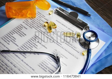 Medical stethoscope, clipboard, pills and coat on the table, close-up