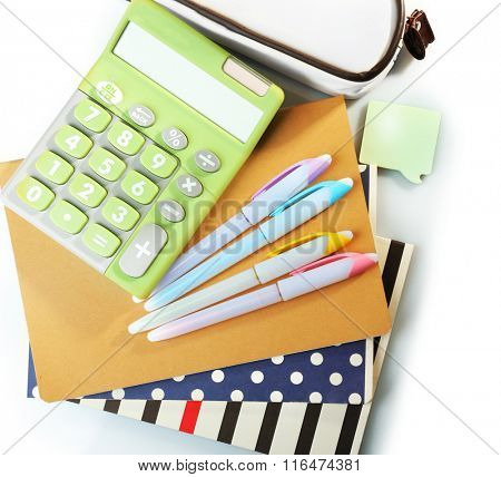 A pile of stylish notebooks and stationary, isolated on white background