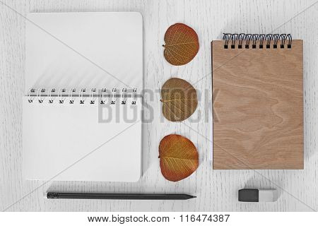 Notebooks with pencil, eraser and dry leaves on a table