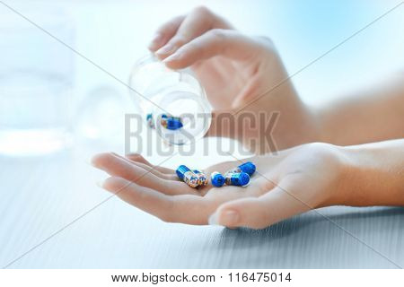 Woman spills blue medical capsules  to her hand, close up