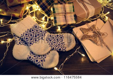 Warm woolen socks with Christmas gifts and decorations on wooden background, close up