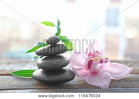 Spa stones with bamboo and pink orchid on wooden background