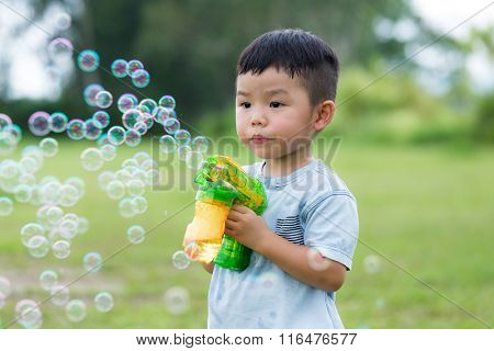 Kid hold with bubble blower at park
