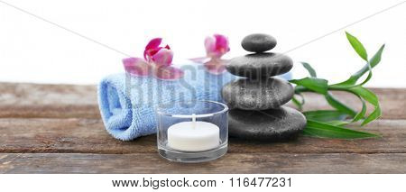 Spa stones with towel, candle, bamboo and purple orchids on white background