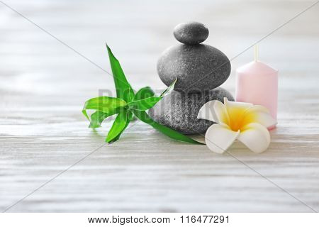 Spa stones with candle, bamboo and tropical flower on light wooden background