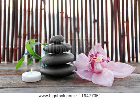 Spa stones with bamboo, candle and pink orchid on wooden background