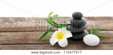 Spa stones with candle, bamboo and tropical flower on white background