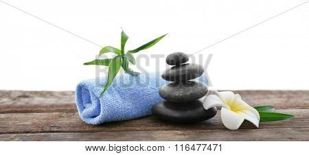 Spa stones with towel, bamboo and tropical flower on white  background