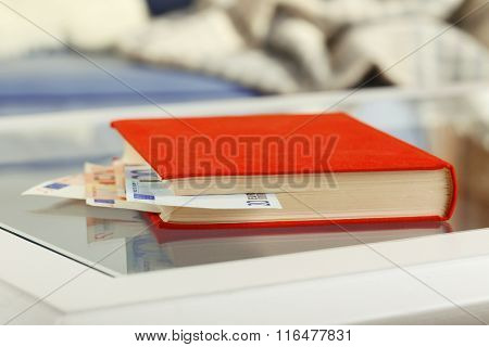 Red book with hidden euro banknotes on glass table
