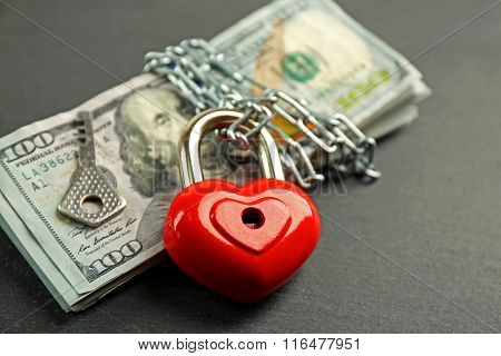 Dollars currency with heart shaped lock and chain on gray  background