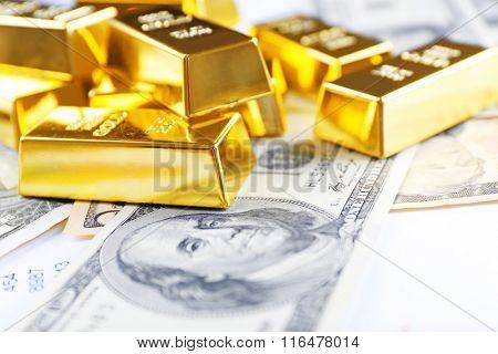 Gold bars on dollar banknotes, close up