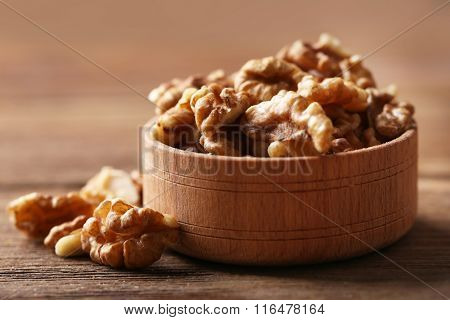 Walnut kernels in the wooden bowl on the table, close-up
