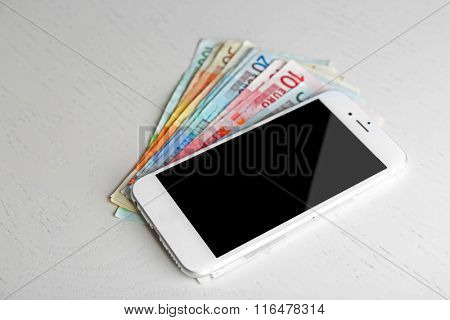 Smart phone on euro banknotes over light table. Internet earning concept