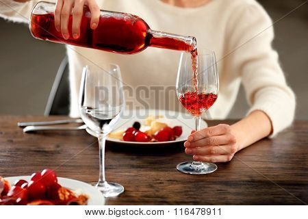 Young woman pouring pink wine into glass on the table