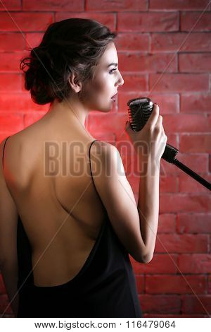 Beautiful brunette singing woman  on brick wall background, backside view