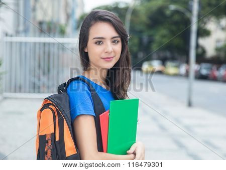 Smiling Caucasian Female Student With Blue Shirt In The City