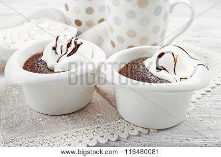 Chocolate lava cake with ice-cream and dotted cups on the table