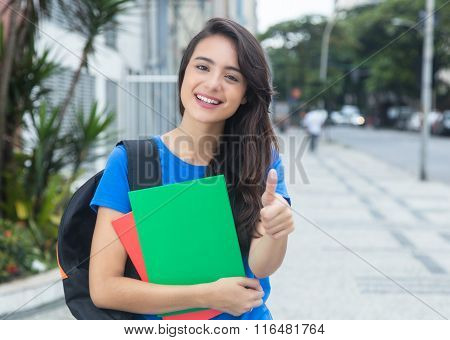Caucasian Female Student With Blue Shirt Showing Thumb In The City