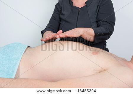 Therapist Performing Reiki On Man On Stomach