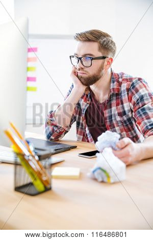 Thoughtful young man with beard in plaid shirt working and crumpling paper in the office