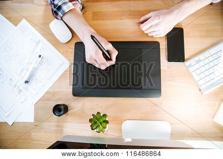 Top view of table of graphic designer using black pen tablet with stylus