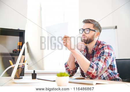 Serious focused young bearded designer in checkered shirt looking and checking blueprint in office