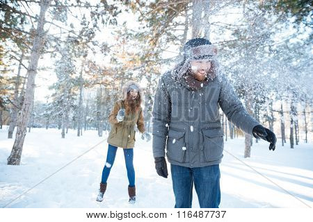 Cheerful young woman playing snowballs with her boyfriend in winter park