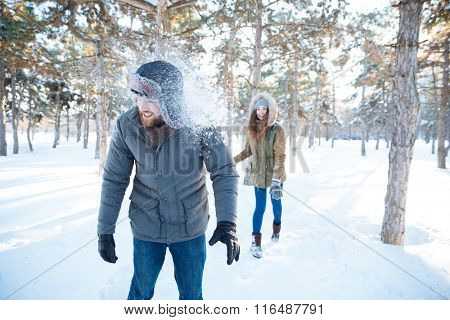 Joyful pretty young woman thowing snowballs in handsome happy young man in winter park