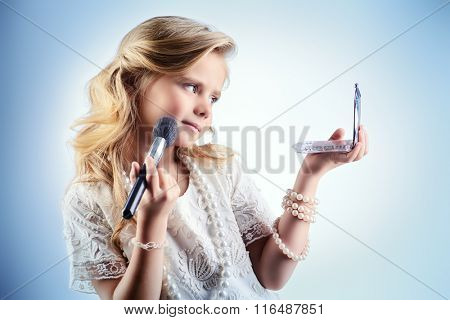 Elegant little girl with beautiful blonde hair looking to herself in the mirror and smiles. Kids fashion. Cosmetics, accessories.