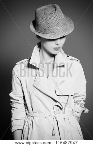 Black-and-white portrait of an elegant fashion model posing at studio in a coat and hat. Beauty, fashion. Business style.