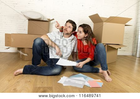Happy American Couple Sitting On Floor Moving In New House Looking Blueprints
