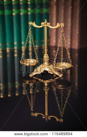 Symbol of law and justice, law and justice concept, golden scales in front of a row of books
