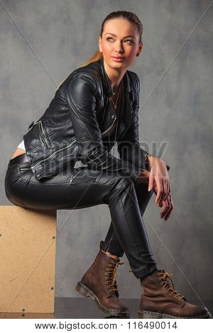 young attractive blonde rocker in leather posing smiling seated on a box, while looking away