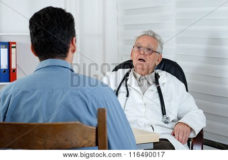 Male Patient Having Consultation With Old Doctor In Consulting Room