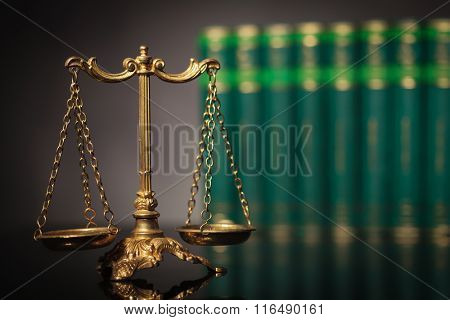 law and justice concept, antique golden scale in front of a row of law books in studio