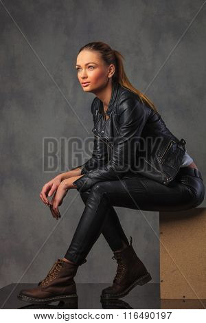 sexy blonde rocker in leather posing seated in a box, resting, in studio background looking away