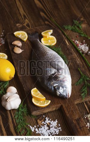 Delicious fresh sea fish on dark wooden background. Healthy food, diet or cooking concept