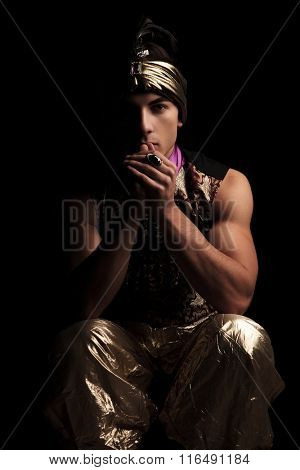 dark portrait of man in golden carnival costume seated in studio background with hands touching