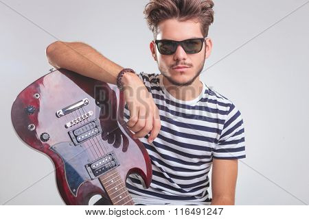 portrait of young rocker wearing sunglasses, pose while resting his hand on an electric guitar in studio background