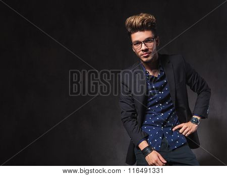 smart young man wearing glasses pose in dark studio background with hand on waist looking at the camera