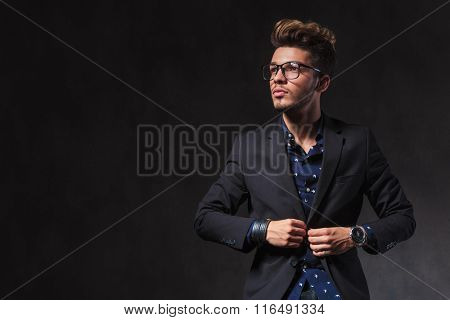 skinny young man wearing glasses is fixing his jacket while looking up in dark studio background