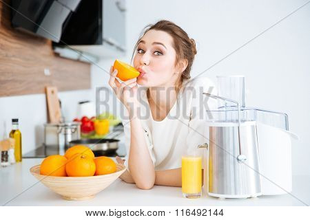 Cute charming young woman making juice and eating oranges on the kitchen