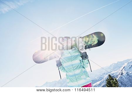 Female snowboarder wearing colorful helmet, blue jacket, grey gloves and pink pants standing standing with snowboard in her hands and preparing for ride - snowboarding concept