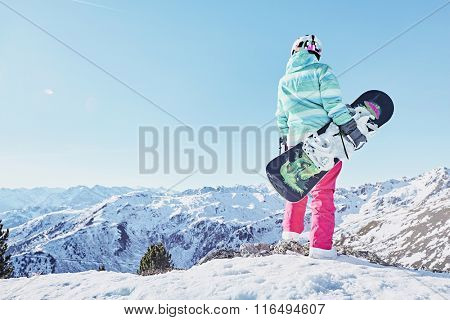 Back view of female snowboarder wearing colorful helmet, blue jacket, grey gloves and pink pants standing with snowboard in one hand and enjoying alpine mountain landscape - snowboarding concept