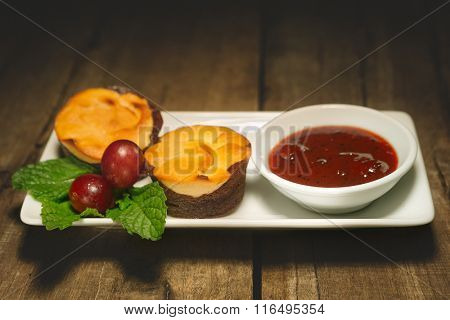 Curd sweet chocolate muffins on a plate with jam on wooden table