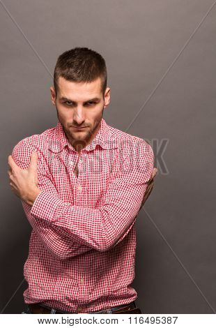 Man hugging himself in studio